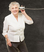 Portrait of senior woman hearing with metal tin can against a gr — Stock Photo