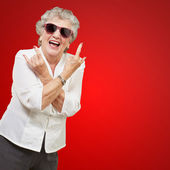 Senior woman wearing sunglasses doing funky action — Photo