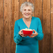 Senior woman holding popcorn — Stock Photo