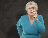 Portrait of senior woman looking through a magnifying glass agai — Stock Photo