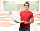 Portrait of young student man holding laptop in classroom — Stockfoto