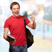 Homme jeune étudiant en colère rudesse une feuille à la salle de classe — Photo