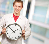 Portrait of a doctor holding a clock — Stock Photo