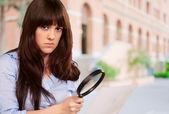 Ritratto di una ragazza che con una lente di ingrandimento e carta — Foto Stock