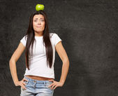 Portrait of young woman holding green apple on her head against — Stock Photo