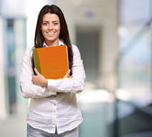 Young girl holding orange book — Stock Photo