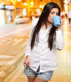 Portrait of young woman drinking at night city — Stock Photo
