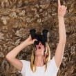 Woman looking through binoculars and pointing up — Stock Photo
