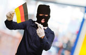 Man wearing a robber mask and holding airplane miniature and fla — ストック写真