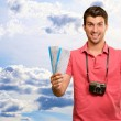 Stock Photo: Man holding boarding pass and airplane