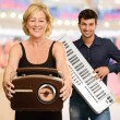 Woman Holding Radio Infront Of Man Holding Piano — Stock Photo