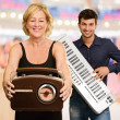 Woman Holding Radio Infront Of Man Holding Piano — Stock Photo #14856255