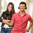 Young Man Enjoying Music And Happy Woman Behind — Stockfoto