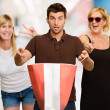 Man Holding Shopping Bag In Front Of Two Happy Women — Stock Photo #14858517