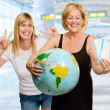 Mature Woman Holding Globe In Front Of Happy Young Woman — Stock Photo