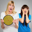 Woman Holding Dartboard In Front Of Shocked Woman — Stock Photo