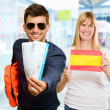 Royalty-Free Stock Photo: Man Holding Boarding Pass In Front Woman Holding Spain Flag