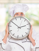 Worried chef hiding behind a clock — Stock Photo