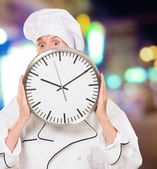 Female chef hiding behind a clock — Stock Photo