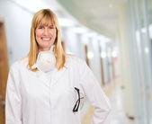 Kadın doktor boyun çevresinde koruyucu maske ile — Stok fotoğraf