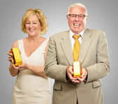 Two Senior Couple Holding Goldbar — Stock Photo