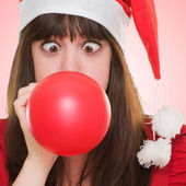 Christmas woman blowing a balloon with her eyes crossed — Stok fotoğraf