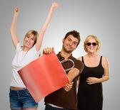 该名男子手持两个快乐的女性在购物袋 — 图库照片