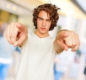 Porträt des jungen Mannes mit der Hand zeigen — Stockfoto