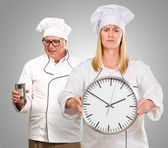 Female Chef Holding Clock In Front Of Male Chef — Stock Photo