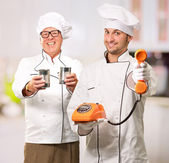 Portrait Of Two Happy Chef While Holding Tin, Telephone — Stock Photo