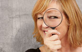 Woman using a magnifying glass — Stock Photo