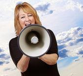Woman screaming on a megaphone — Stock Photo