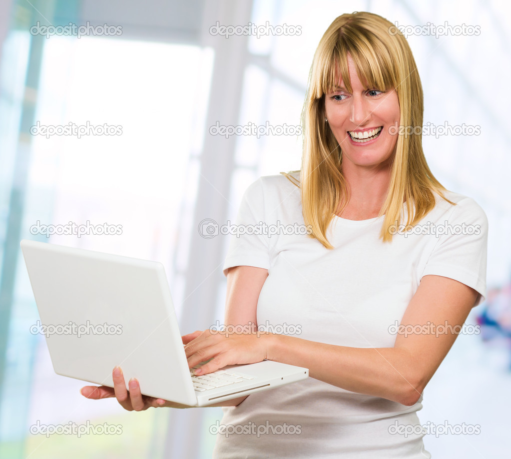 Happy Woman Looking At Laptop against an abstract background, indoor — Stock Photo #14855437