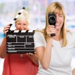 Two Happy Woman Holding Clapper Board And Camera — Stock Photo #14866867