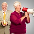 Senior Woman Shouting In Megaphone In Front Of Businessman Holdi — Stock Photo #14867019