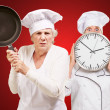 Foto Stock: Two Female Chef Holding Saucepan And Clock