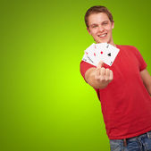 Portrait of a young male holding four aces — Stock Photo