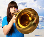 Portrait of a young girl blowing trumpet — Stockfoto