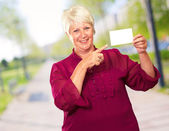 Portrait Of A Senior Woman Pointing To The Blank Card — Stock Photo