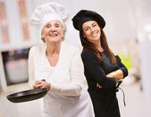 Senior Chef Holding Pan In Front Of Smiling Woman — Stock Photo