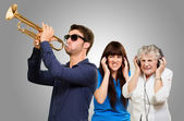 Young Man Blowing Trumpet And Women Getting Irritation Wearing — Stock Photo