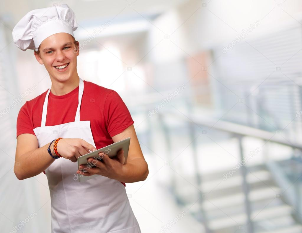 Young cook holding a digital tablet, indoor  Stock Photo #14860367