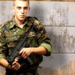 Handsome soldier holding gun — Stock Photo
