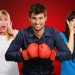 Man With Boxing Gloves And Scared Woman Standing Behind - Foto Stock