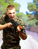 Portrait of an angry soldier aiming — Stock Photo