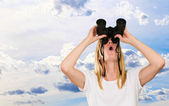 Woman lookin up using binoculars — Stock Photo