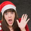 Surprised woman wearing a christmas hat — Stock Photo #16302293