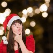 Stock Photo: Woman thinking and wearing a christmas hat