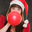 Stock Photo: Woman blowing balloon and wearing a christmas hat