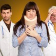 Woman With Neck Brace In Front Of Doctors - Stock Photo
